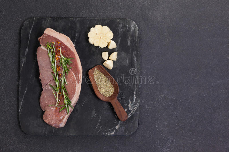 Sirloin chop, garlic and spices on black slate plate. Against wooden background stock photos