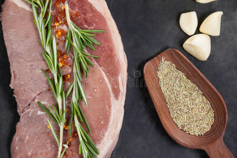 Sirloin chop, garlic and spices on black slate plate. Against wooden background royalty free stock images