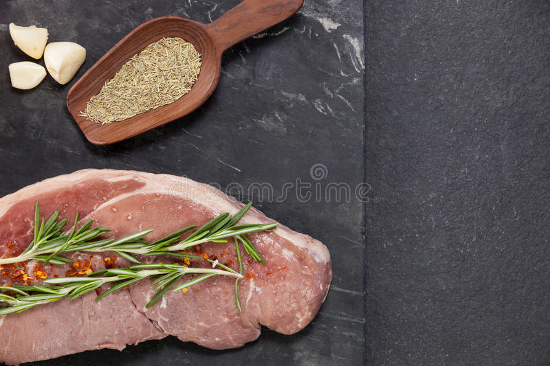Sirloin chop, garlic and spices on black slate plate. Against wooden background royalty free stock photography