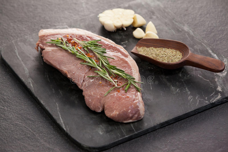 Sirloin chop, garlic and spices on black slate plate. Against wooden background stock photo