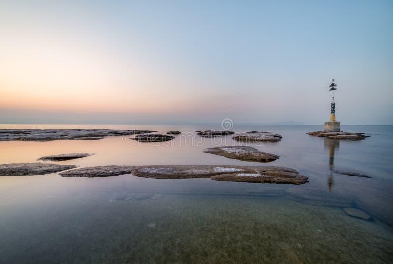 Infinite rock flat on garda lake. Sirmione beach by night, rocks flat and sunset color toward infinity on garda lake stock photography