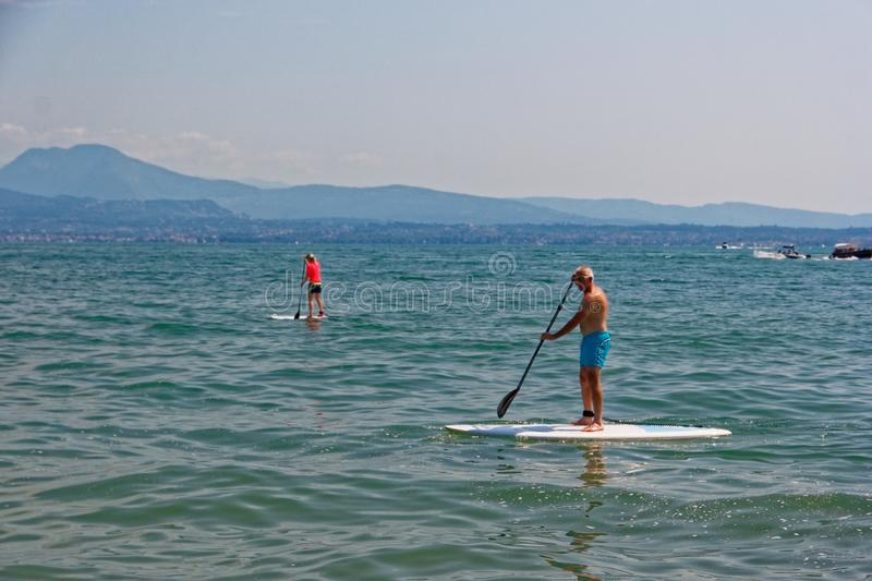 Sirmione, Italië 17 Augustus 2018: Meer Garda mensen op de surfplank stock afbeeldingen