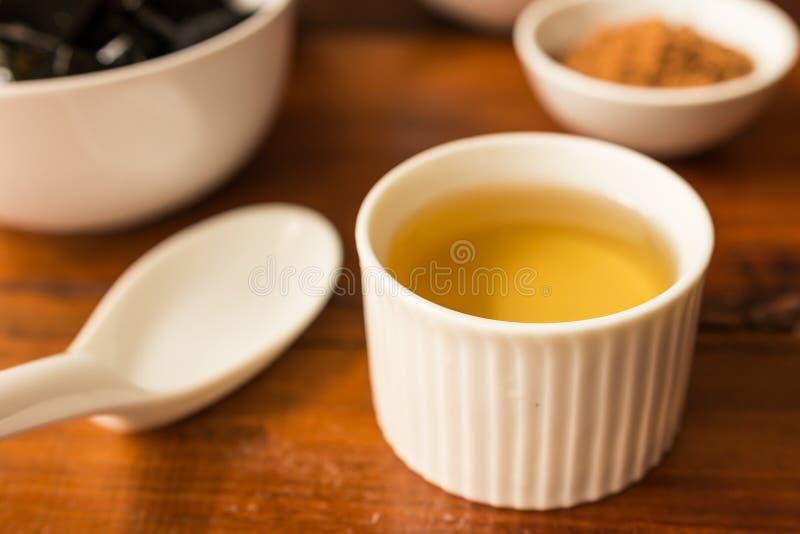 Sirop - sirop dans une petite tasse blanche de gelée d'herbe photographie stock