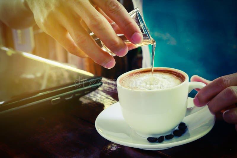 Sirop de versement dedans dans la tasse de café chaude de Latte photos stock