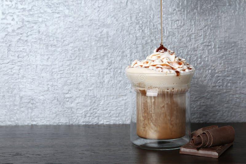 Sirop doux de versement dans la tasse en verre avec du café savoureux sur la table en bois photos stock