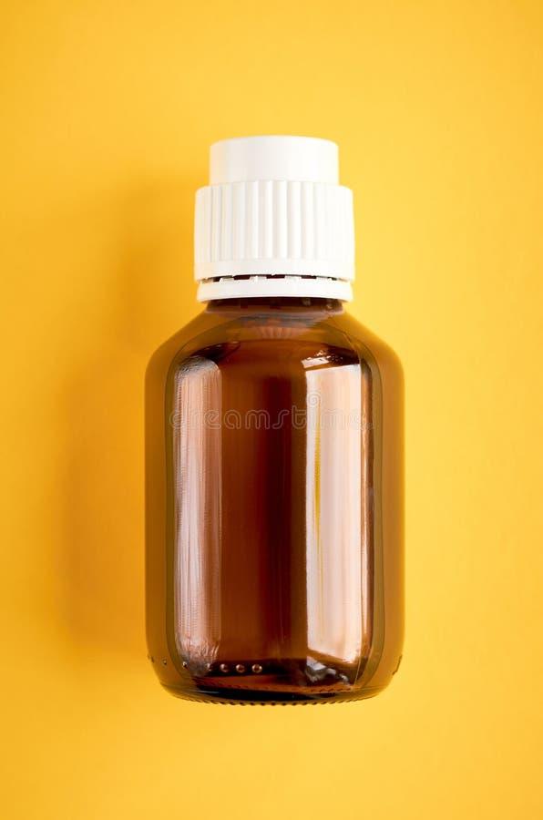 Sirup in der Glasflaschenzusammensetzung auf gelbem Hintergrund lizenzfreies stockbild