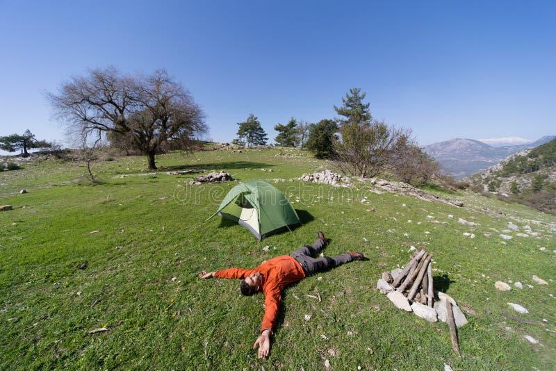 Sirva acampar con una tienda en las montañas en el verano imagen de archivo