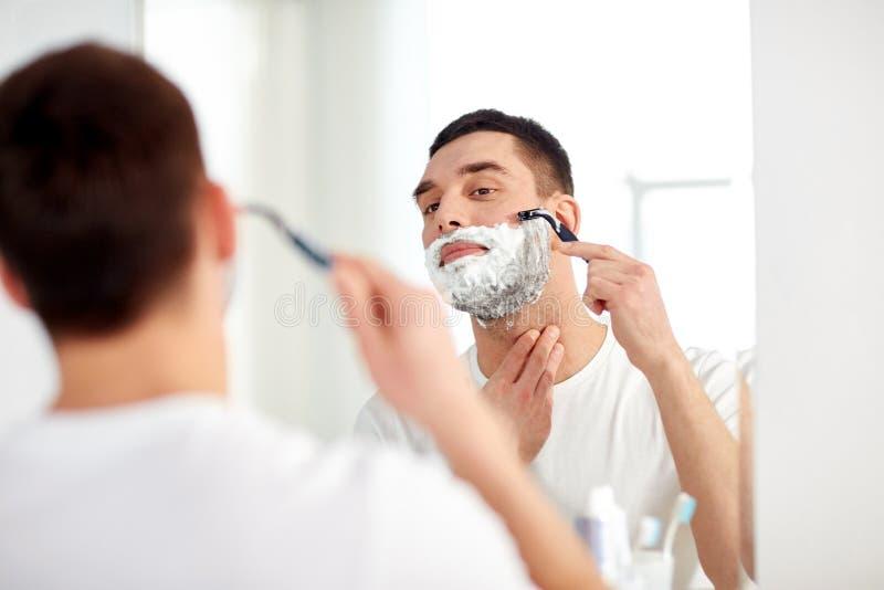 Sirva afeitar la barba con la hoja de afeitar en el cuarto de baño foto de archivo libre de regalías