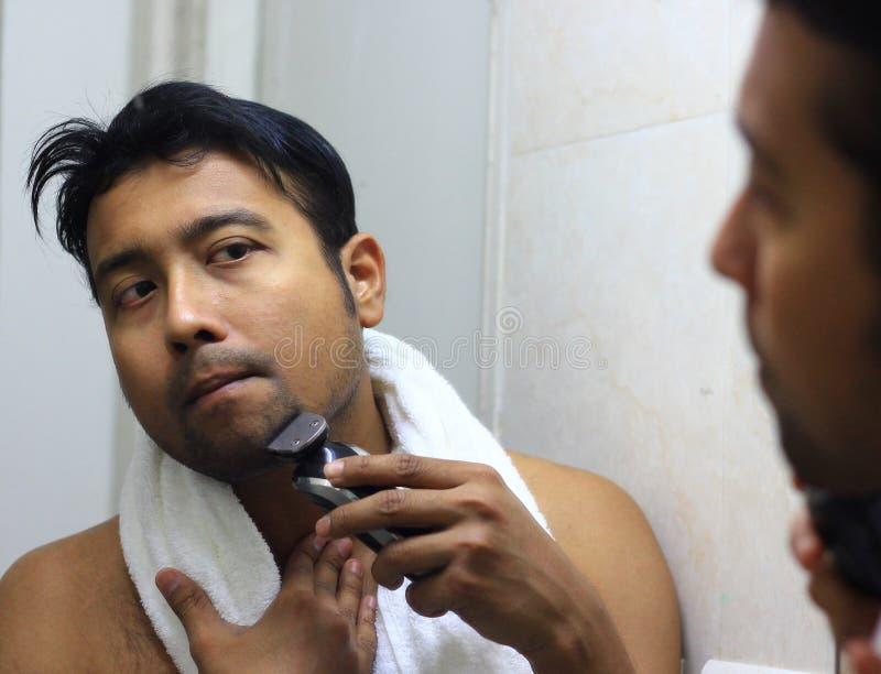 Sirva al asiático lookingIndian después de su aspecto delante de una belleza del espejo que diseña forma de vida Afeitar rutina foto de archivo libre de regalías