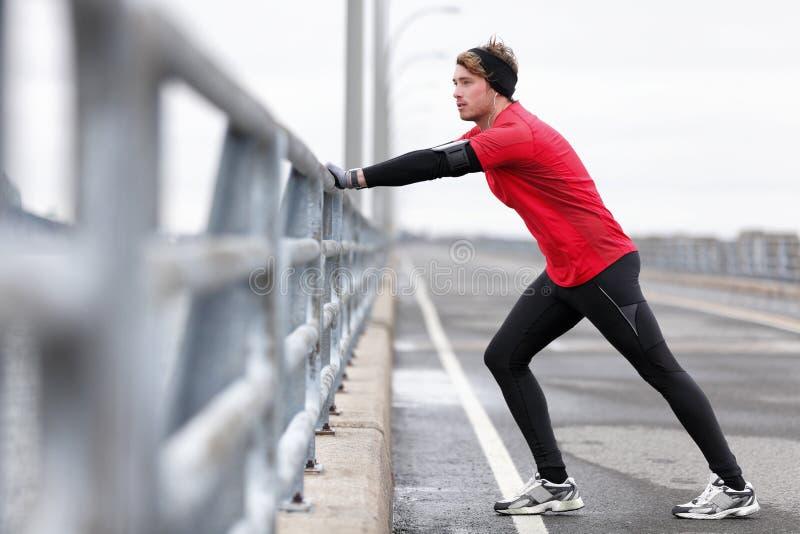 Sirva al atleta que estira las piernas en funcionamiento al aire libre del invierno foto de archivo libre de regalías