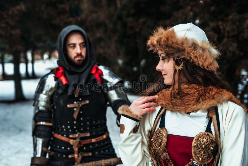 Sirva al caballero en armadura y mujer en traje histórico imagenes de archivo