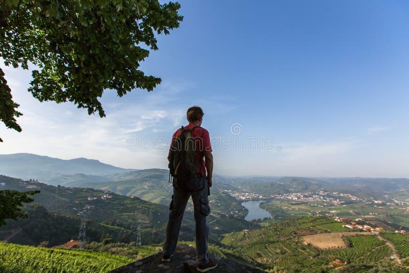Sirva al caminante con la mochila que se coloca encima de una montaña y que disfruta de la vista del valle del Duero imagenes de archivo