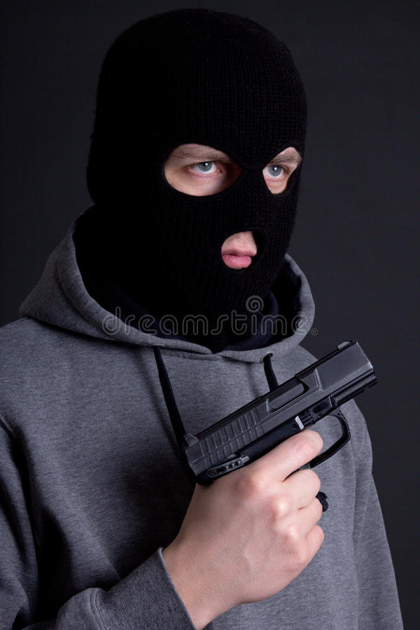 Sirva al criminal en máscara negra con el arma sobre gris imágenes de archivo libres de regalías