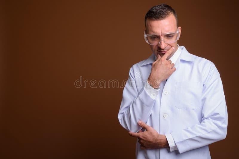Sirva al doctor que lleva los vidrios protectores contra fondo marrón foto de archivo