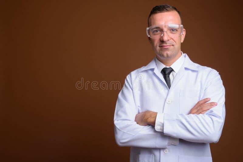 Sirva al doctor que lleva los vidrios protectores contra fondo marrón fotografía de archivo