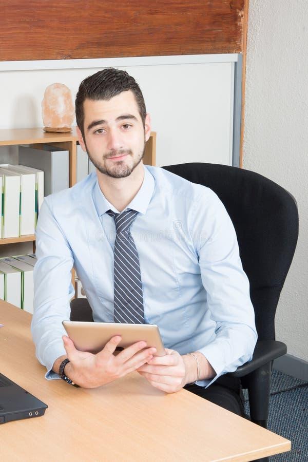 Sirva al empleado que presenta para la foto en el escritorio del lugar de trabajo en oficina corporativa fotografía de archivo libre de regalías