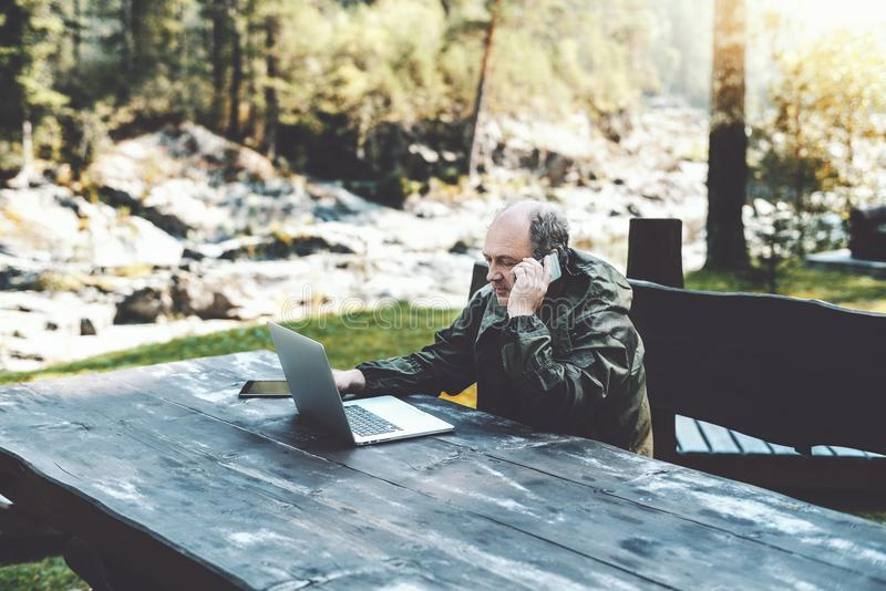 Sirva al empresario con el ordenador portátil que habla en el teléfono en bosque foto de archivo