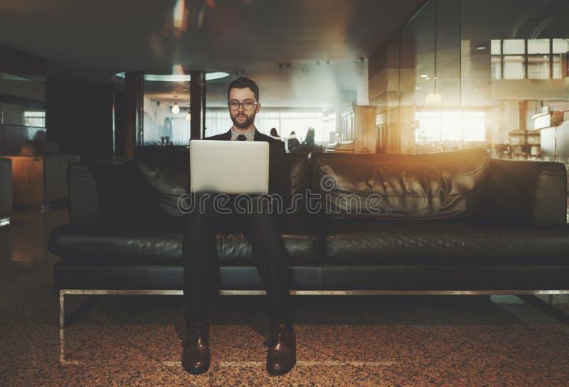 Sirva al empresario en el sofá de la oficina con el ordenador portátil imagen de archivo libre de regalías
