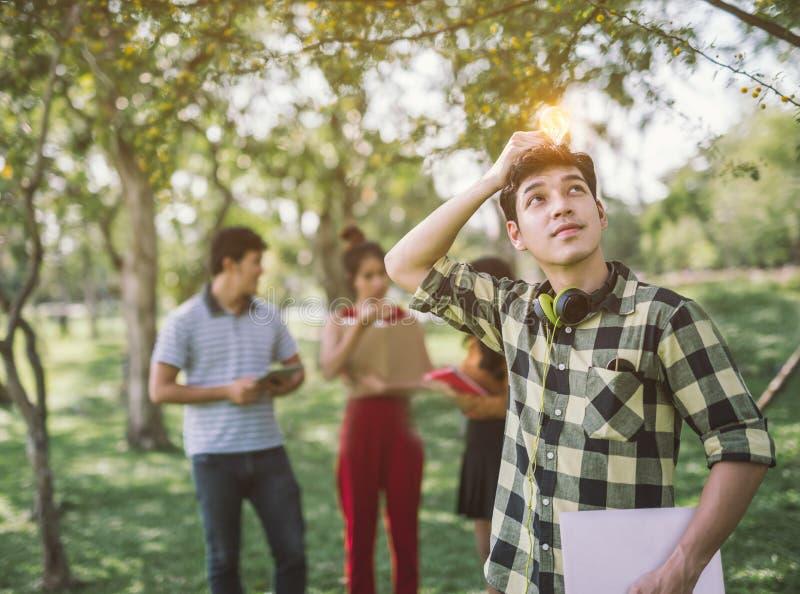 Sirva al estudiante adolescente que se sostiene al bulbo iluminado La bombilla piensa que las ideas crean fotografía de archivo libre de regalías