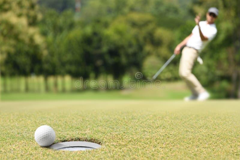 Sirva al golfista que anima después de una pelota de golf en verde imagen de archivo libre de regalías