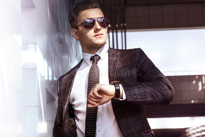 Sirva al hombre de negocios en chaqueta de las gafas de sol y átelo contra la perspectiva de paisaje urbano fotos de archivo libres de regalías