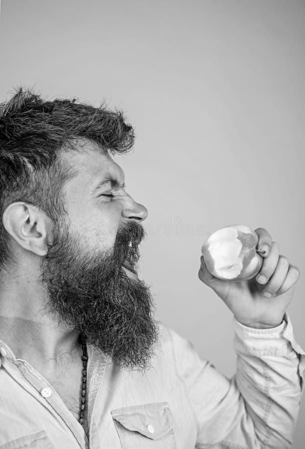 Sirva al inconformista hermoso con la barba larga que come la manzana Yo nutrición de la dieta del hombre de las manzanas de amor imagenes de archivo