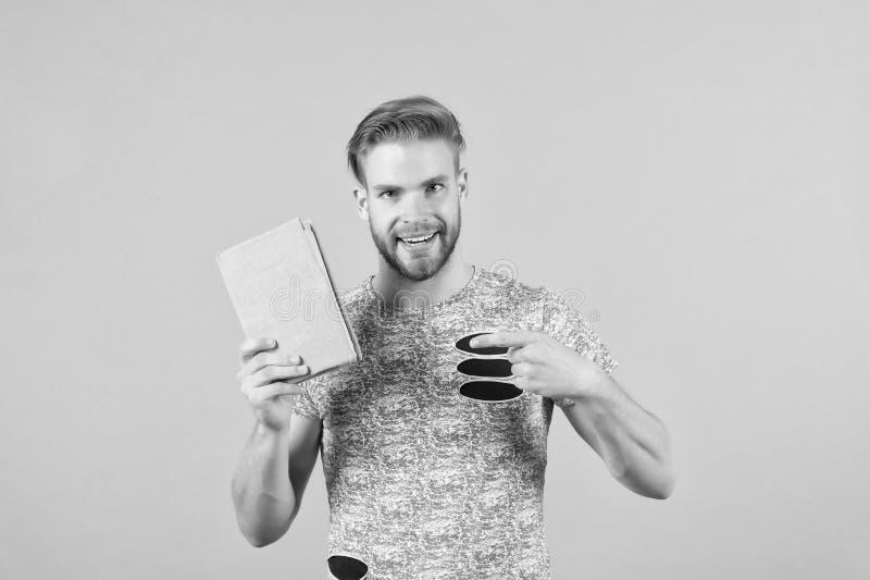 Sirva al individuo sin afeitar barbudo en camisa elegante que señala en el libro La cara sonriente del hombre recomienda el libro imagenes de archivo