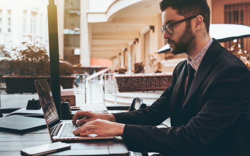 Sirva al patrón en vidrios con el ordenador portátil en restaurante de la calle fotografía de archivo libre de regalías