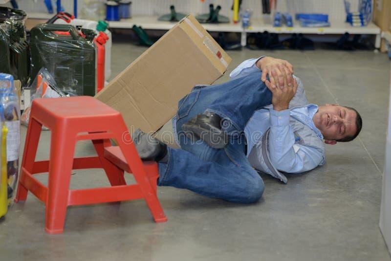 Sirva al trabajador con accidente del concepto de la lesión de rodilla en el trabajo foto de archivo