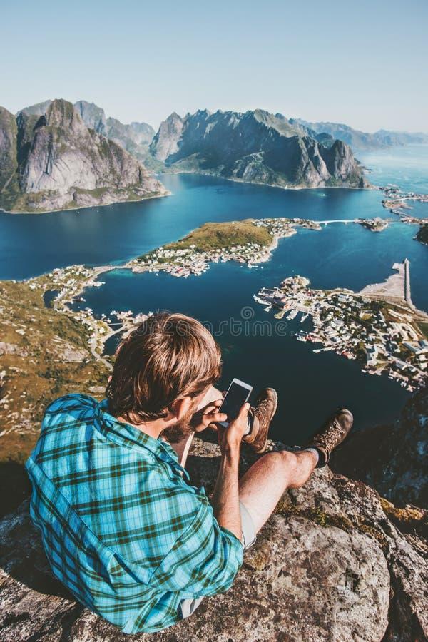 Sirva al turista que usa el smartphone que se relaja en el borde del acantilado imagen de archivo
