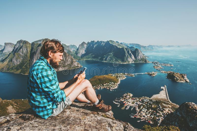 Sirva al turista que usa el smartphone que se sienta en el borde del acantilado imagen de archivo
