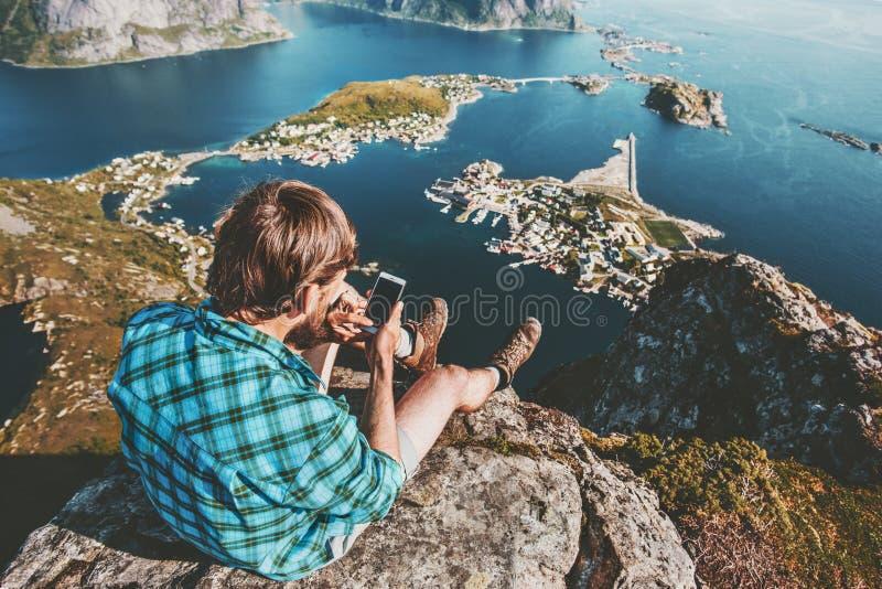 Sirva al viajero que usa el smartphone que se relaja en el top de la montaña foto de archivo libre de regalías