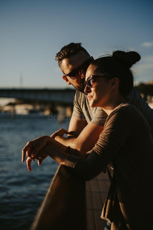 Sirva besar a su esposa en la puesta del sol por el río imagen de archivo libre de regalías