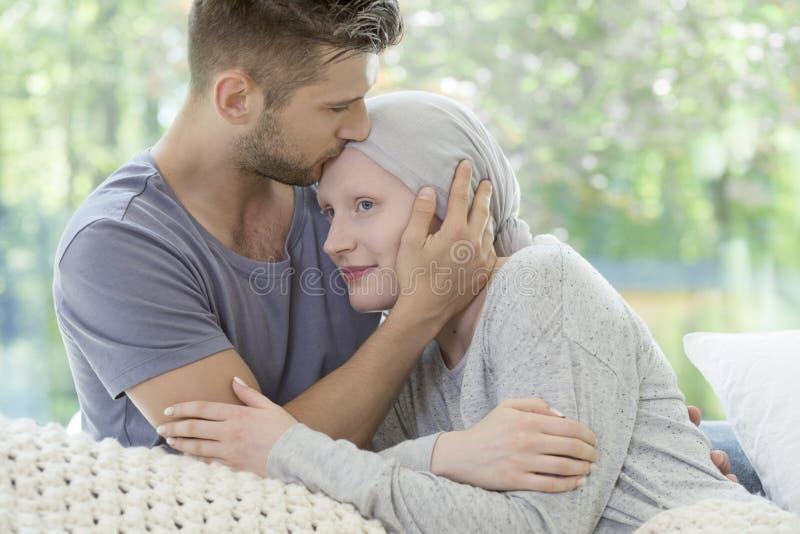 Sirva besar a su novia enferma en la frente Ayuda durante fotos de archivo