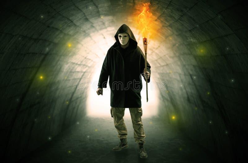 Sirva caminar con la antorcha ardiente en un t?nel oscuro fotografía de archivo libre de regalías