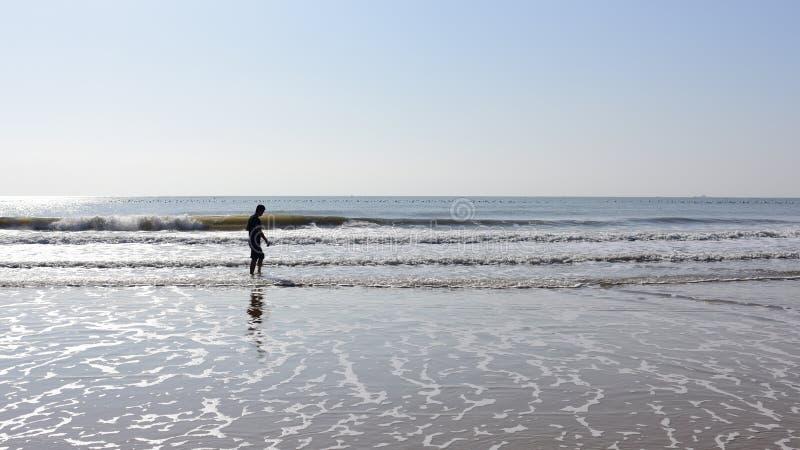 Sirva caminar en agua de mar con la cabeza abajo fotografía de archivo