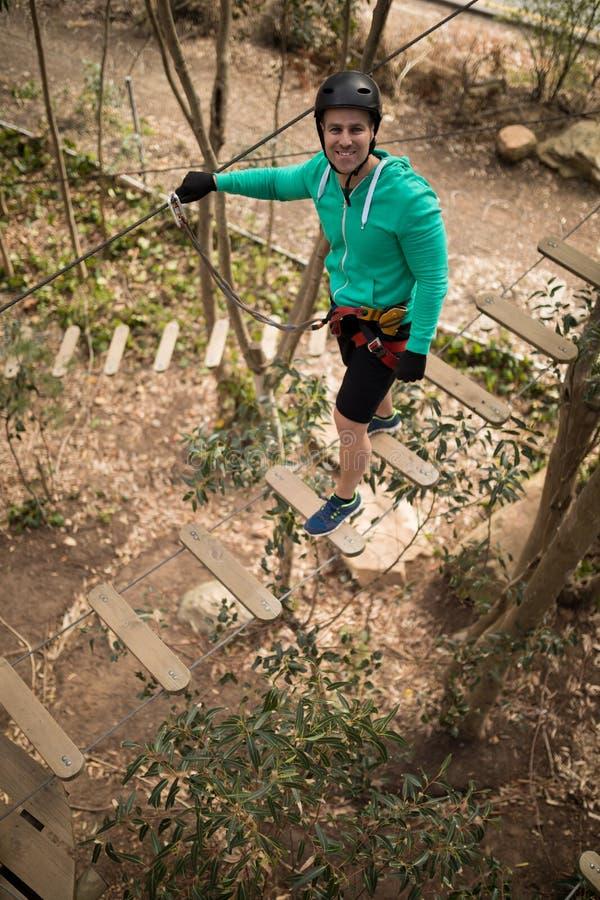 Sirva caminar en el puente de cuerda en parque de la aventura fotos de archivo