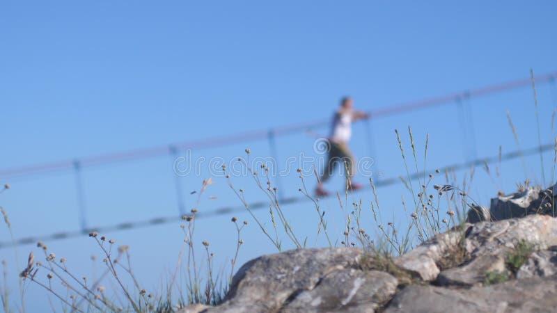 Sirva caminar en la cuerda en el puente de ejecución largo sobre el abismo en la hierba en primero plano imagen de archivo libre de regalías