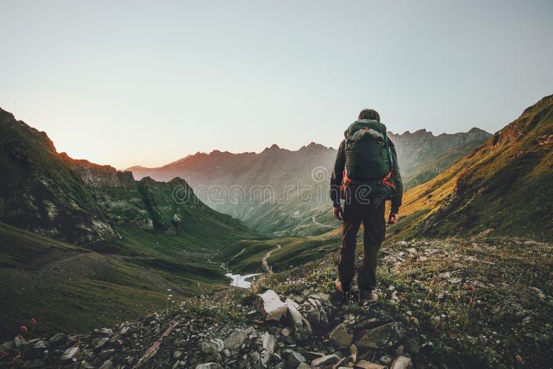 Sirva caminar en las montañas de la puesta del sol con la mochila pesada imagen de archivo