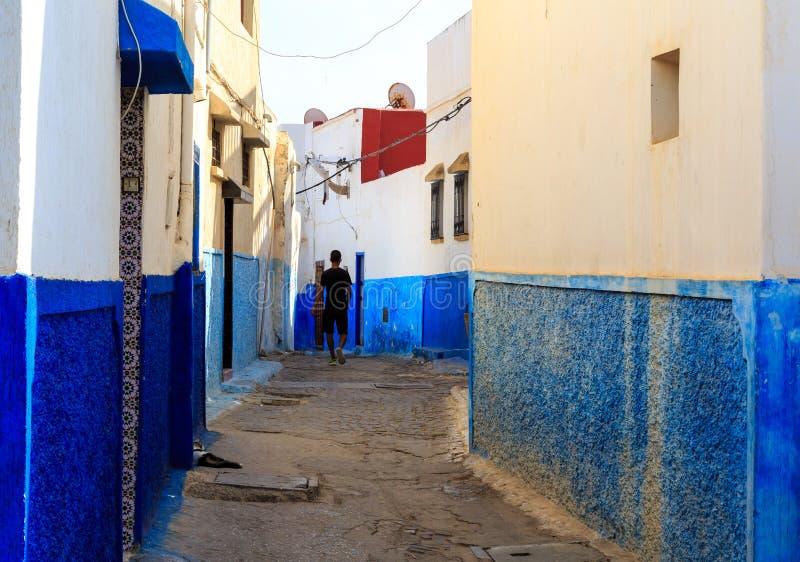Sirva caminar en las pequeñas calles en azul y blanco en el kasbah foto de archivo