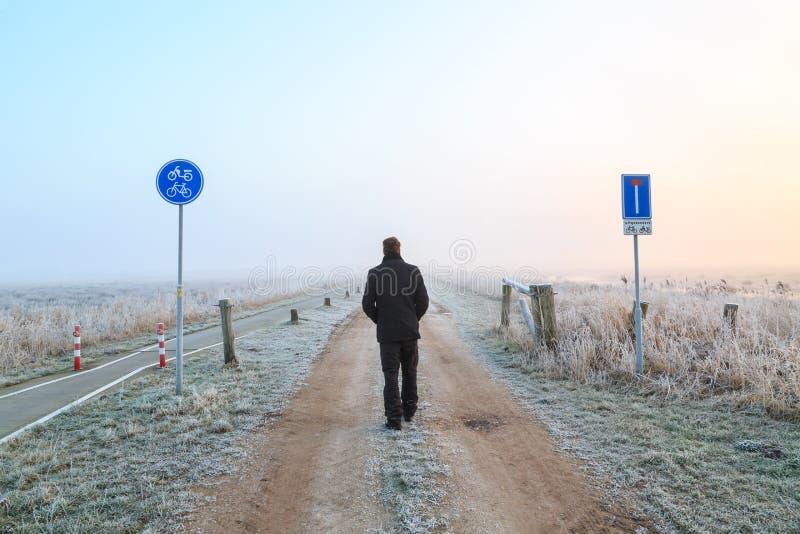 Sirva caminar en un camino de la arena en un paisaje del invierno fotos de archivo libres de regalías
