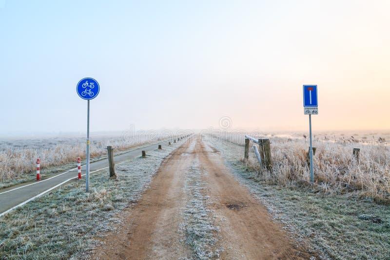 Sirva caminar en un camino de la arena en un paisaje del invierno imagen de archivo libre de regalías