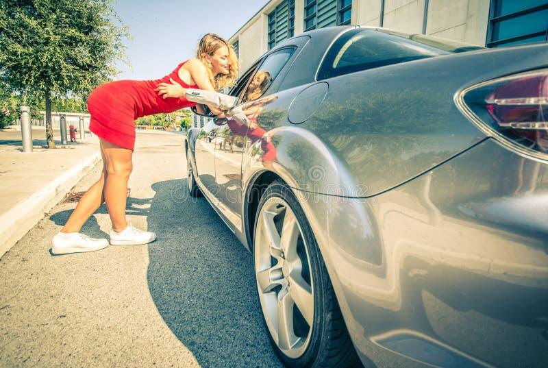 Sirva coger a una muchacha hermosa con su coche deportivo fotos de archivo libres de regalías
