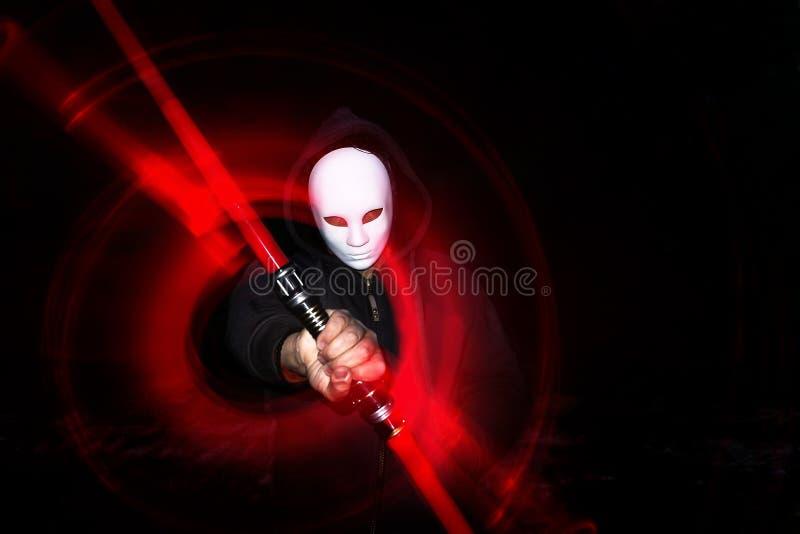 Sirva con la máscara que lleva a cabo el lightsaber fotografía de archivo libre de regalías