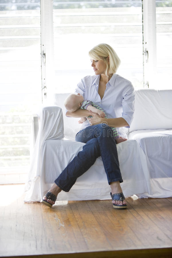 Sirva de madre al bebé durmiente de la explotación agrícola en el sofá en sitio asoleado imagen de archivo