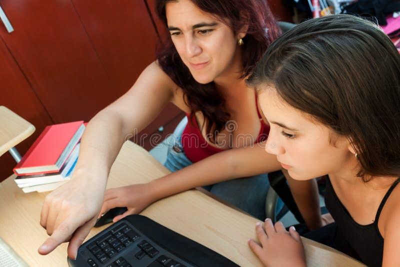 Sirva de madre enseñando a su hija a cómo utilizar un ordenador fotos de archivo