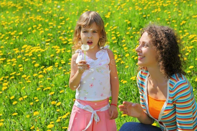 Sirva de madre a los juegos con la muchacha que respiración en el diente de león imagenes de archivo