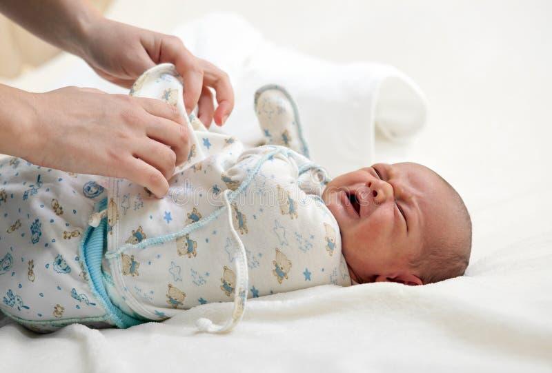 Sirva de madre a poner la ropa en su bebé recién nacido foto de archivo