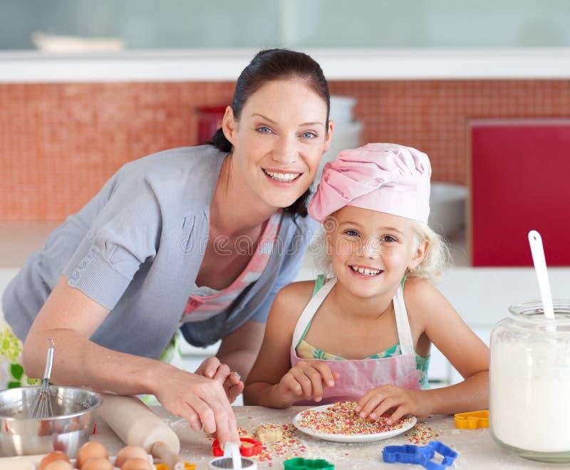Sirva de madre y childing en la cocina que sonríe en la cámara imagenes de archivo