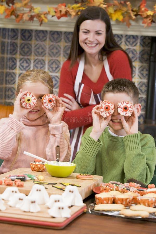 Sirva de madre y dos niños en Víspera de Todos los Santos en cocina foto de archivo libre de regalías